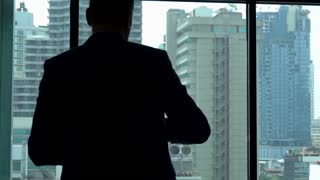 Businessman standing in his hotel room and throwing money, slow motion shot at 240fps