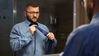 Businessman standing in the bathroom and getting ready for work