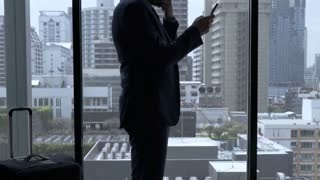 Businessman standing in the hotel room and receives bad news on smartphone