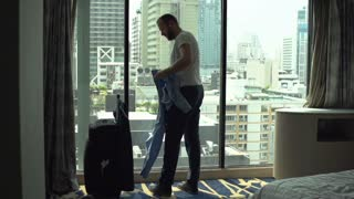 Businessman take off his shirt and hangs it on rack, slow motion shot at 120fps
