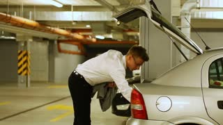 Businessman takes luggage from his car and leaving