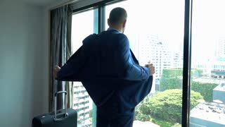 Businessman takes off his jacket in his fancy apartment, slow motion shot at 240fps