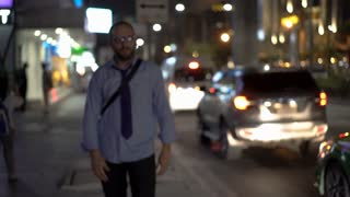 Businessman walking at night on busy street and using smartphone