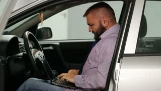 Businessman working on laptop in his car and looks very angry