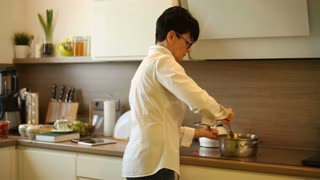 Businesswoman cooking meal in her kitchen after work