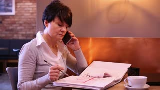Businesswoman with cellphone and documents working at caffe