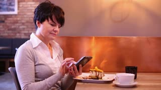 Businesswoman with smartphone sitting at caffe
