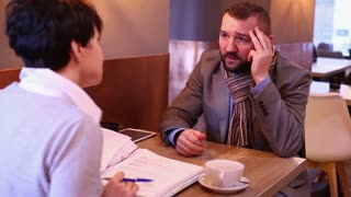 Couple businesspeople in cafe with documents, worried man