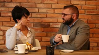 Couple businesspeople talking and drinking coffee in cafe