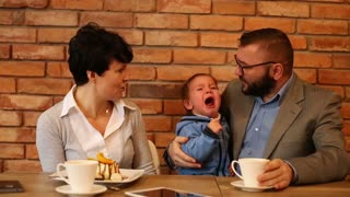 Couple businesspeople with a cry baby are sitting in cafe
