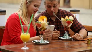 Couple having a date in the restaurant and looking on smartphone
