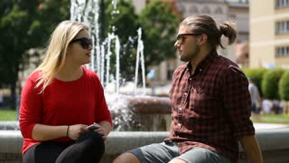 Couple sitting next to the fountain and boy sneezing all the time