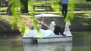 Couple using pedal boat on the lake and relaxing, slow motion shot at 240fps