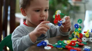 Cute, little boy playing with colorful blocks and having fun
