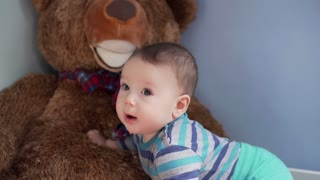 Cute little boy playing with the big toy bear and has a lot of fun