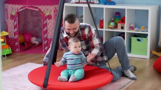 Dad play with son in playroom on the swing kids, and swinging kid on it