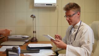Doctor checking something on tablet and talking to the camera