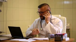 Doctor having a medical examination on the cellphone and working in the office