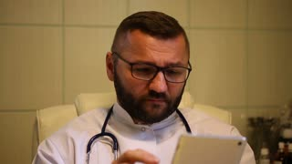 Doctor sitting in the office and browsing internet on tablet