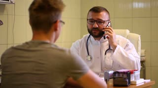 Doctor speaking on cellphone and tells good news to the patient
