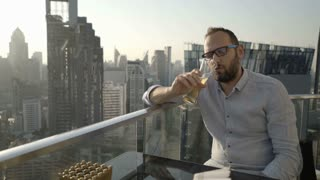 Drunk man sitting in skybar and drinking beer