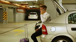 Elegant businessman sitting in car's trunk and chatting on cellphone