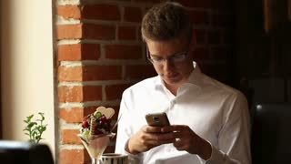 Elegant man sitting in the cafe and texting messages on smartphone