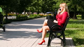 Elegant woman wearing heels and chatting on cellphone in the park