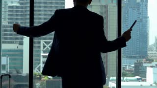 Excited businessman jumping in his apartment, slow motion shot at 240fps