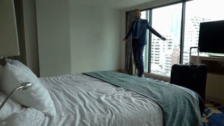 Excited businessman jumping on bed in his hotel room, slow motion shot at 240fps