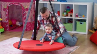 Father play with child in babyroom