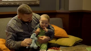 Father play with son on sofa