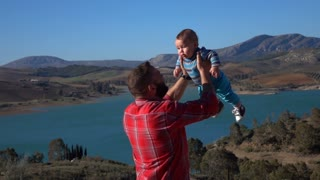 Father Playing With His Little Son Outdoor. Dad Lifting Up His Child At mountains. Slow Motion.