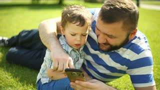 Father sitting with his son on the grass and they are using smartphone