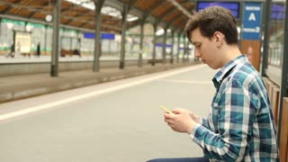 Father texting sms on smartphone while his son is walking on the platform