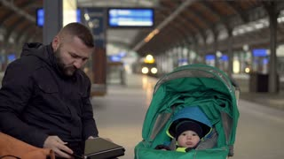 Father using laptop on station with kid