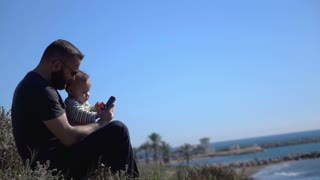 Father using phone to play with son, super slow motion
