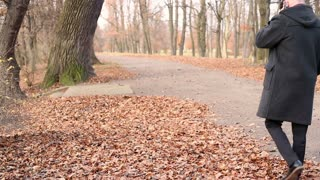 Grown man talking on cellphone, walking in the autumnal park