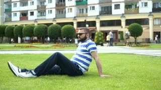 Handsome man sitting on the grass in the park and relaxing