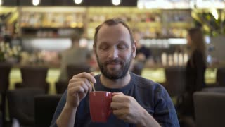 Handsome man smiling to the camera in the cafe and drinking cappuccino