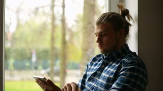 Handsome man with mud bun sitting next to the window and using tablet
