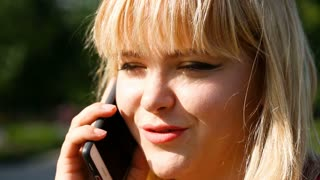 Happy blonde woman chatting on cellphone in the park