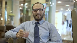 Happy businessman drinking alcoholic drink in pub and talking to the camera