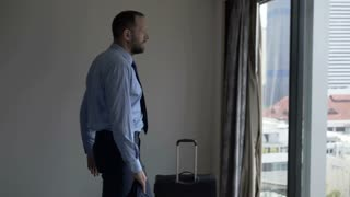 Happy businessman enjoying his time in fancy apartment and admires the view