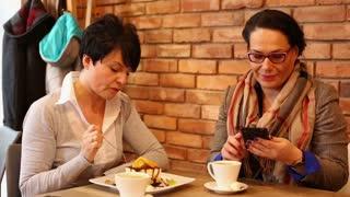 Happy girlfriends using smartphone in cafe