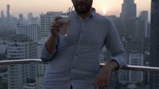 Happy man drinking alcoholic drink on rooftop and speaking to the camera