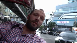 Happy man riding a tuktuk in the city and captures memories, steadycam shot at 240fps