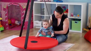 Happy mother play with her adorable baby boy in babyroom