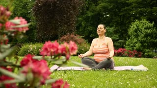 Happy woman expecting baby and doing yoga in the garden