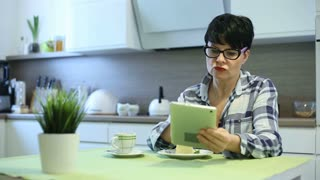 Happy woman relaxing in the kitchen and browsing internet on tablet